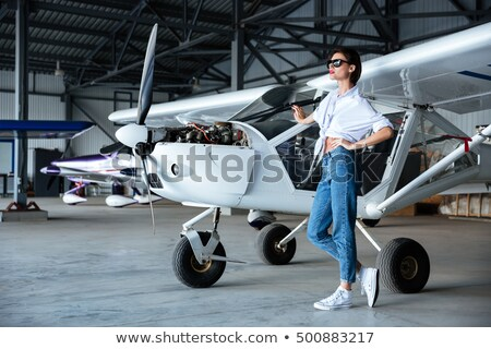 Woman in sunglasses standing near small vintage plane Stock photo © deandrobot