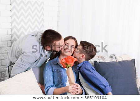 Husband giving wife flowers kissing and smiling Stock photo © monkey_business