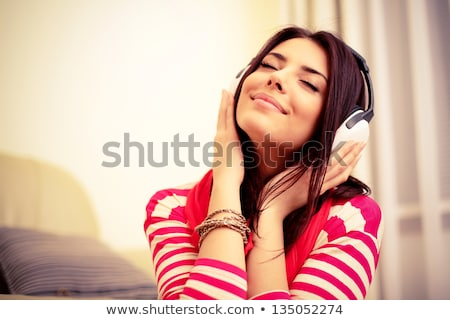 happy young woman listening music with earphones stock photo © deandrobot