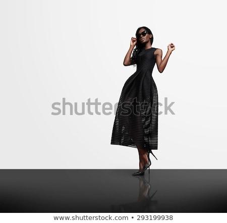 Csinos barna hajú visel fekete ruha pózol kint Stock fotó © acidgrey