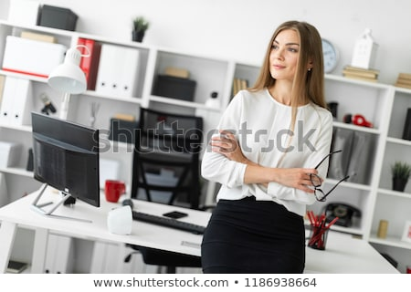 a young girl is standing leaning on a table in the office and holding glasses in her hand stock photo © traimak