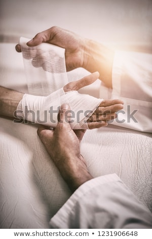 Doctor Tying Bandage On Man's Hand Stock photo © AndreyPopov
