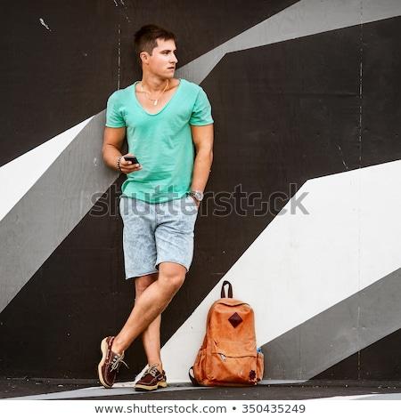 Homme sac à dos permanent rue de la ville mur Voyage Photo stock © dolgachov
