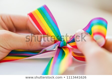hands tying bow of gay pride awareness ribbon Stock photo © dolgachov