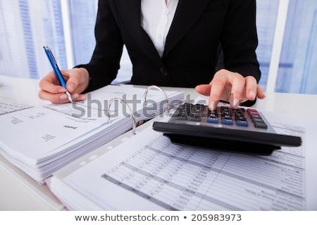 Bills In Front Of Businesswoman Calculating Invoice Stock photo © AndreyPopov