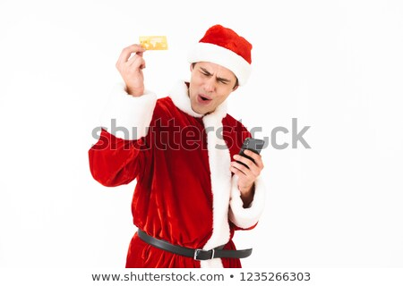 Image of joyous man 30s in santa claus costume holding smartphon Stock photo © deandrobot