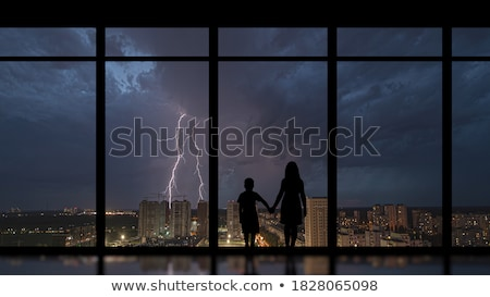 Silhouette of a loving couple against a window with a view of the night city stock photo © galitskaya