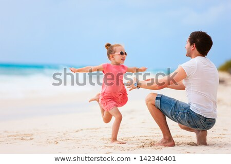 Happy Father Running With Her Daughter On The Beach Stock photo © AndreyPopov