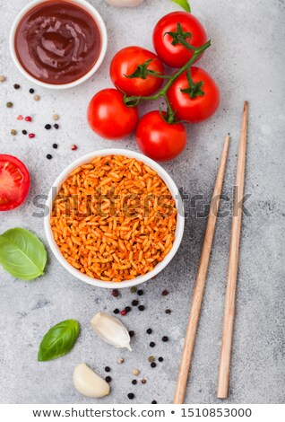 White plate bowl of rice with tomato and basil and garlic and chopsticks on light stone background.  Stock photo © DenisMArt