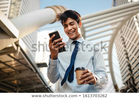 Stock photo: Front view of Asian businessman using mobile phone in the modern office