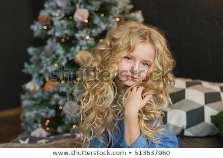 The girl sits on the bed and touches her curly blonde long hair Stock photo © ElenaBatkova