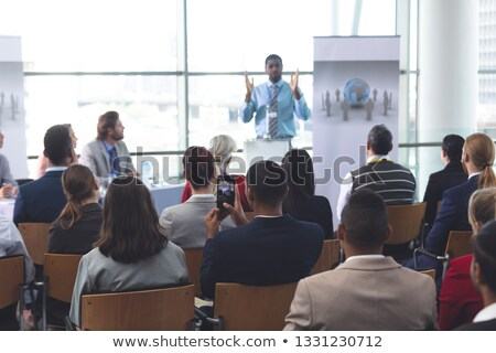 front view of caucasian businessman speaking at a business seminar in office building with american stock photo © wavebreak_media