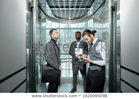 Young well-dressed male entrepreneur using digital tablet in elevator Stock photo © pressmaster