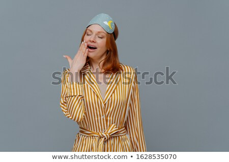 Fatigue sleepy red head woman yawns with opened mouth, wears domestic striped robe and blindfold on  Stock photo © vkstudio