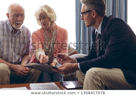 Side view of matured Caucasian male physician interacting with senior Caucasian couple at retirement Stock photo © wavebreak_media