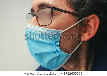 Young male doctor with face mask and glasses Stock photo © Imaagio