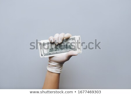 Man holding money dollars in hand in black medical gloves.  Stock photo © Illia