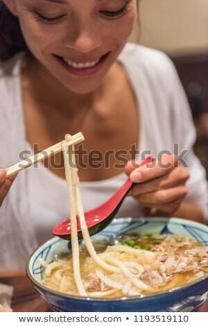 Ramen noodles girl eating soup bowl at japanesese restaurant at night. City travel lifestyle. Stock photo © Maridav