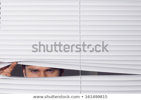 Young man looking through the blind. Stock photo © zurijeta