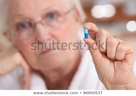 Elderly woman holding a capsule between her fingers Stock photo © photography33