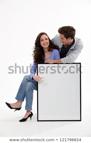 Playful young couple pointing the blank white baord Stock photo © get4net