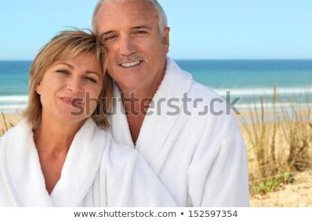 Mature couple in bathrobe on the beach Stock photo © photography33
