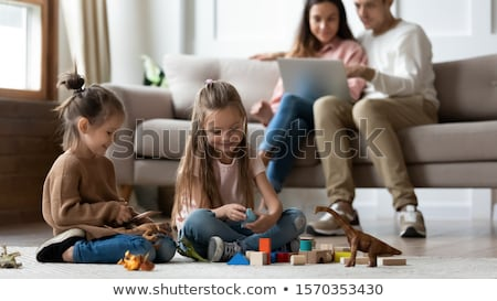 Stock photo: Cute Friends lounging on a sofa in a living room