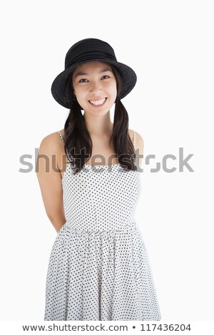 Cheerful woman with a polka dot dress and hat with hands behind her back Stock photo © wavebreak_media
