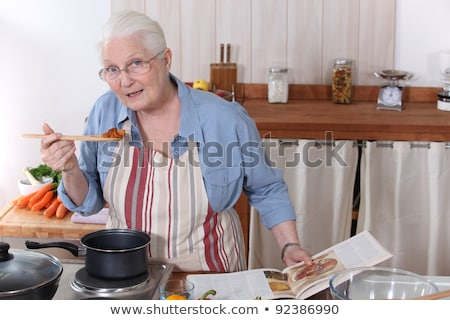 senior citizen cooking with recipe book Stock photo © photography33