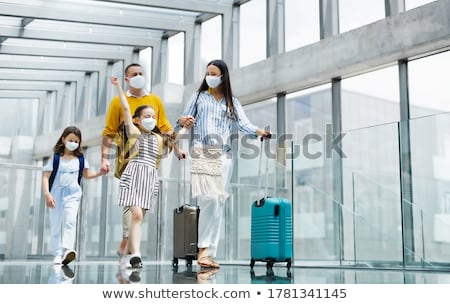 travel woman walking in an airport with luggage stock photo © maridav