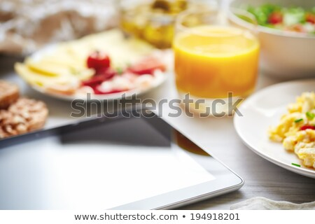 Fresh continental breakfast. Tablet, black screen. stock photo © dariazu