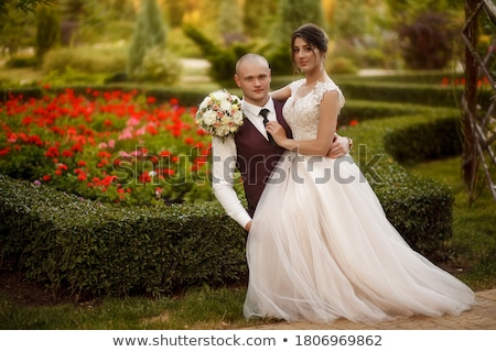 Handsome groom hugging his beautiful wife Stock photo © konradbak