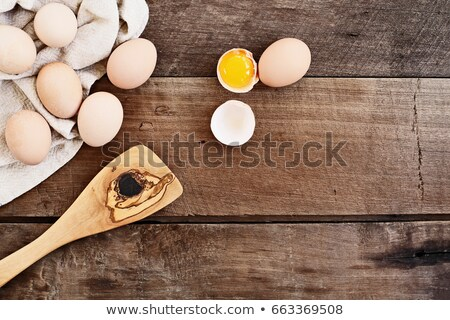 cracked chicken eggs on a wooden table Stock photo © nito