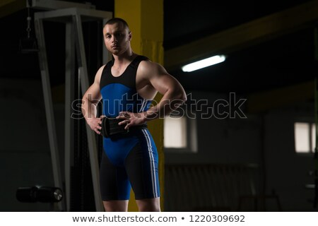 portrait of a handsome athletic man holding barbell stock photo © deandrobot