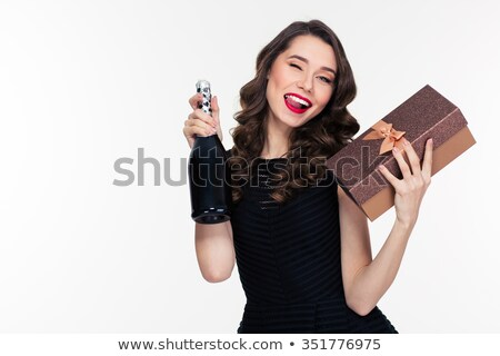 Attractive winking  woman holding bottle of champagne and gift  Stock photo © deandrobot