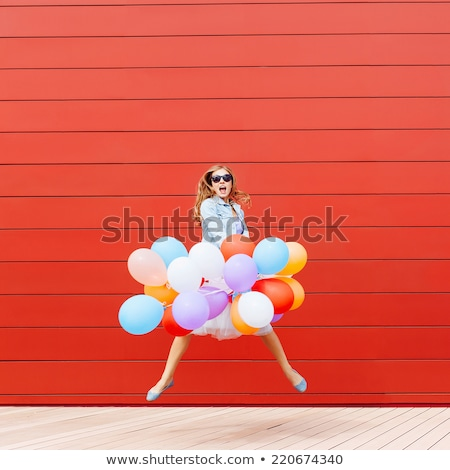 young girl jumping with red balloon stock photo © is2