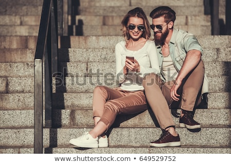 Young Caucasian woman using smart phone while sitting on stairs  Stock photo © Kzenon