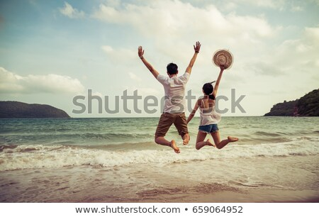 two beautiful young girlfriends jumping on the beach stock photo © massonforstock