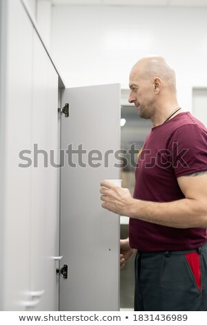 Factory worker opening locker Stock photo © IS2