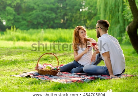 Couple cuddling on picnic blanket Stock photo © IS2