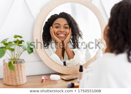 woman in bathrobe applying makeup stock photo © is2