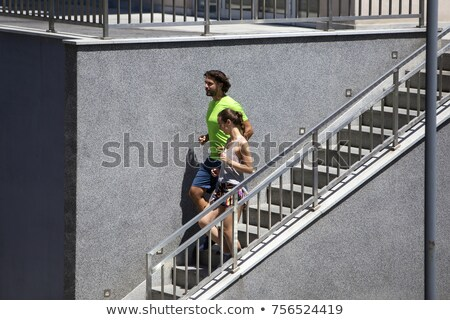 Young couple running down stairs in urban enviroment Stock photo © boggy