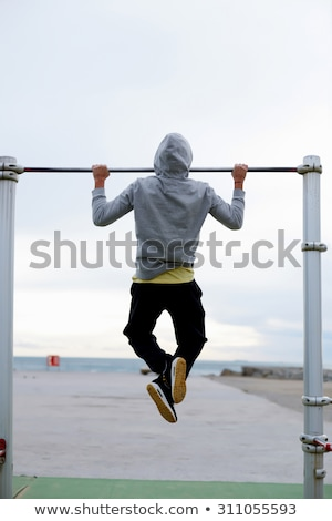 Man doing pull ups on horizontal bar outdoors Stock photo © boggy