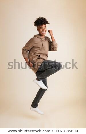 Izgatott fiatal afro amerikai férfi ugrik Stock fotó © deandrobot