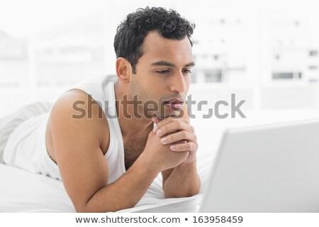 ハンサムな男 · ラップトップを使用して · ベッド · コンピュータ · 笑顔 · 男 - ストックフォト © lopolo