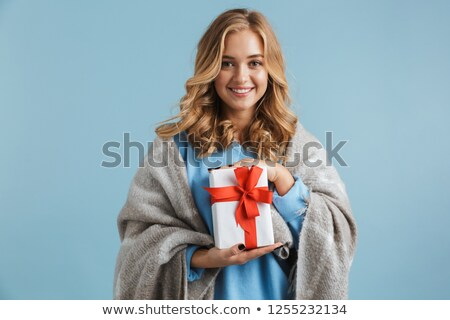 Image of lovely woman 20s wrapped in blanket holding gift box, i Stock photo © deandrobot