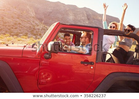 friends with camera driving in convertible car Stock photo © dolgachov