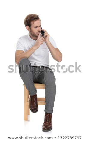 seated man talking on the phone makes the quiet gesture Stock photo © feedough