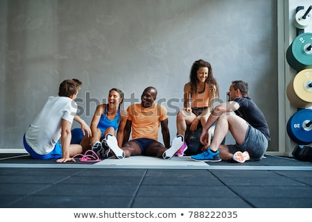 friends in sportswear talking and laughing together while sittin stock photo © boggy