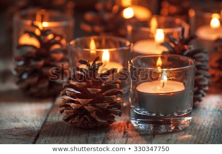pine cone and candles burning on christmas table Stock photo © dolgachov